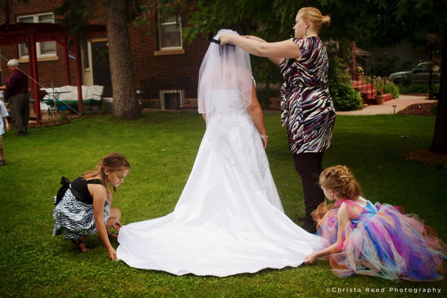 finishing touches on wedding dress in belle plaine Minnesota outdoor wedding