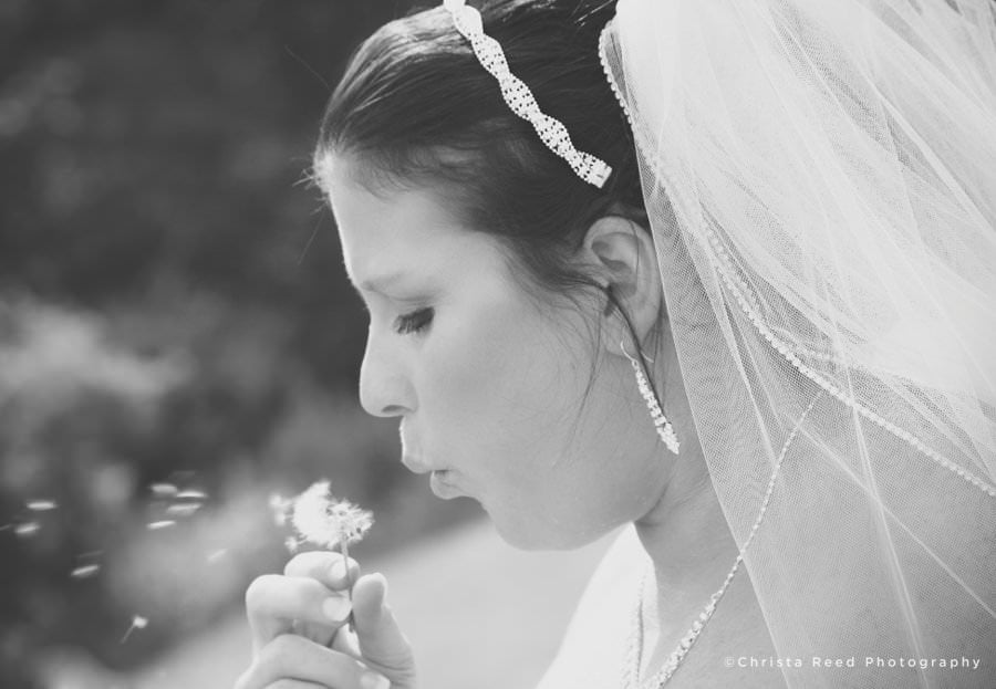 bride makes a wish on a dandelion before her wedding in belle plaine minnesota
