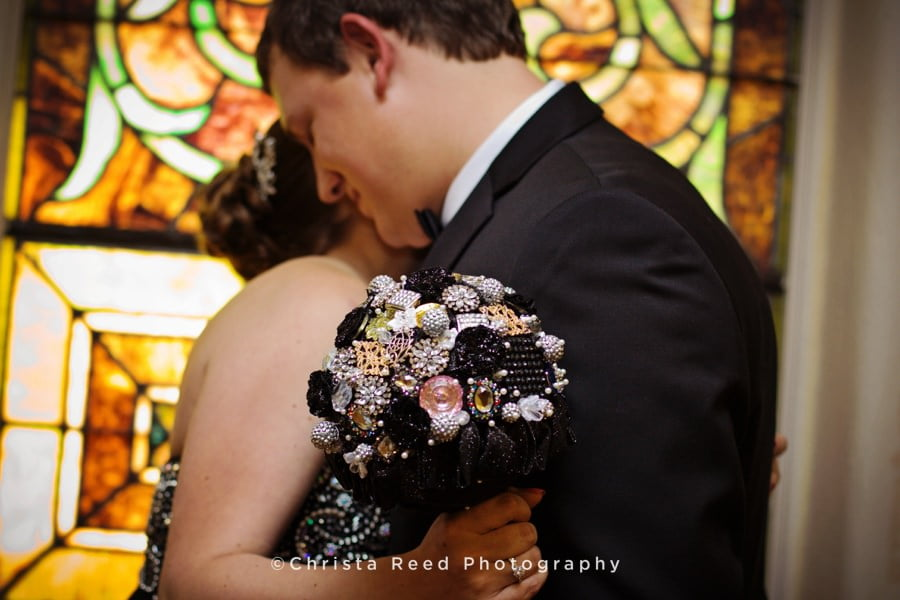the bride holds a brooch bouquet for her evening wedding ceremony in belle plaine minnesota