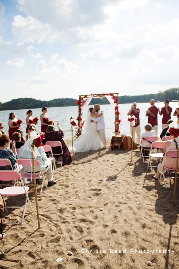 the bride and groom kiss at a beach wedding on the shore of Bryant Lake