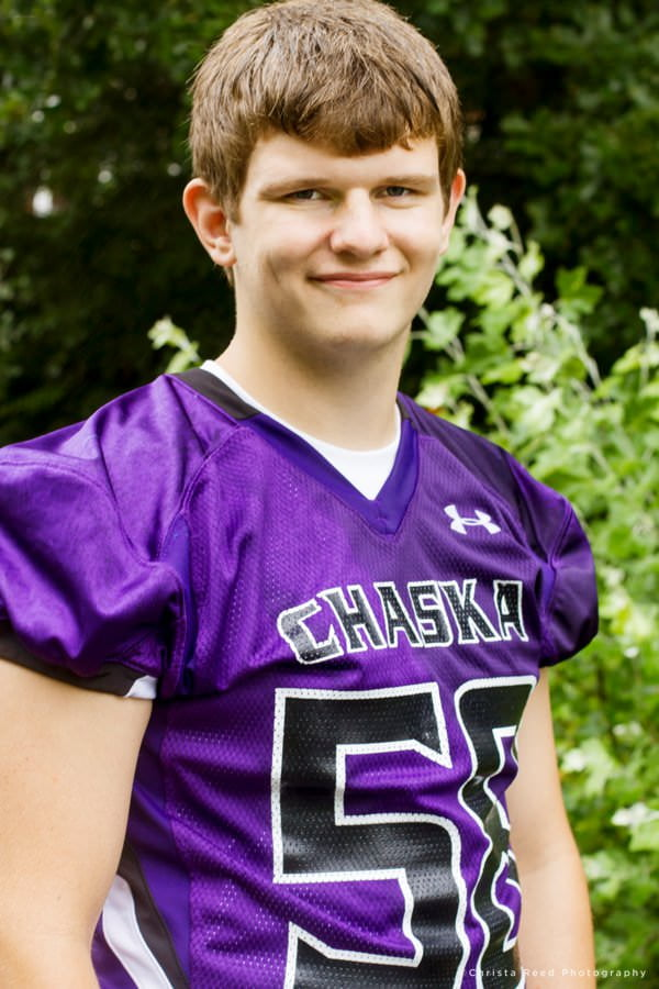senior portrait with purple football jersey by chaska senior photographer