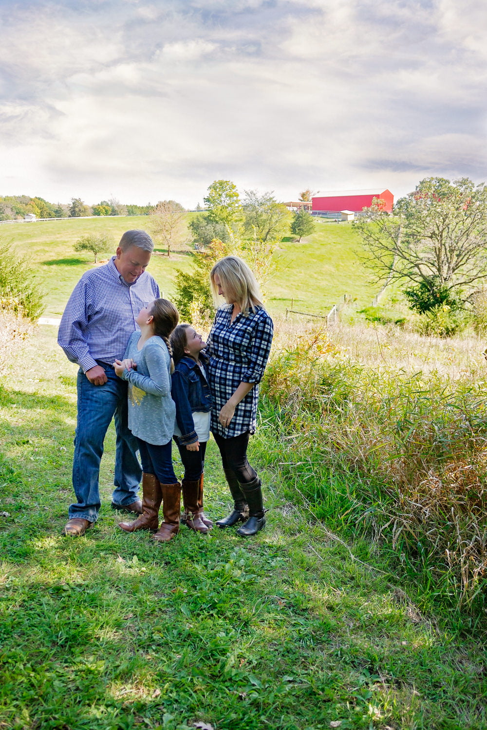 a family stands on a hillside for portraits in minnetrista
