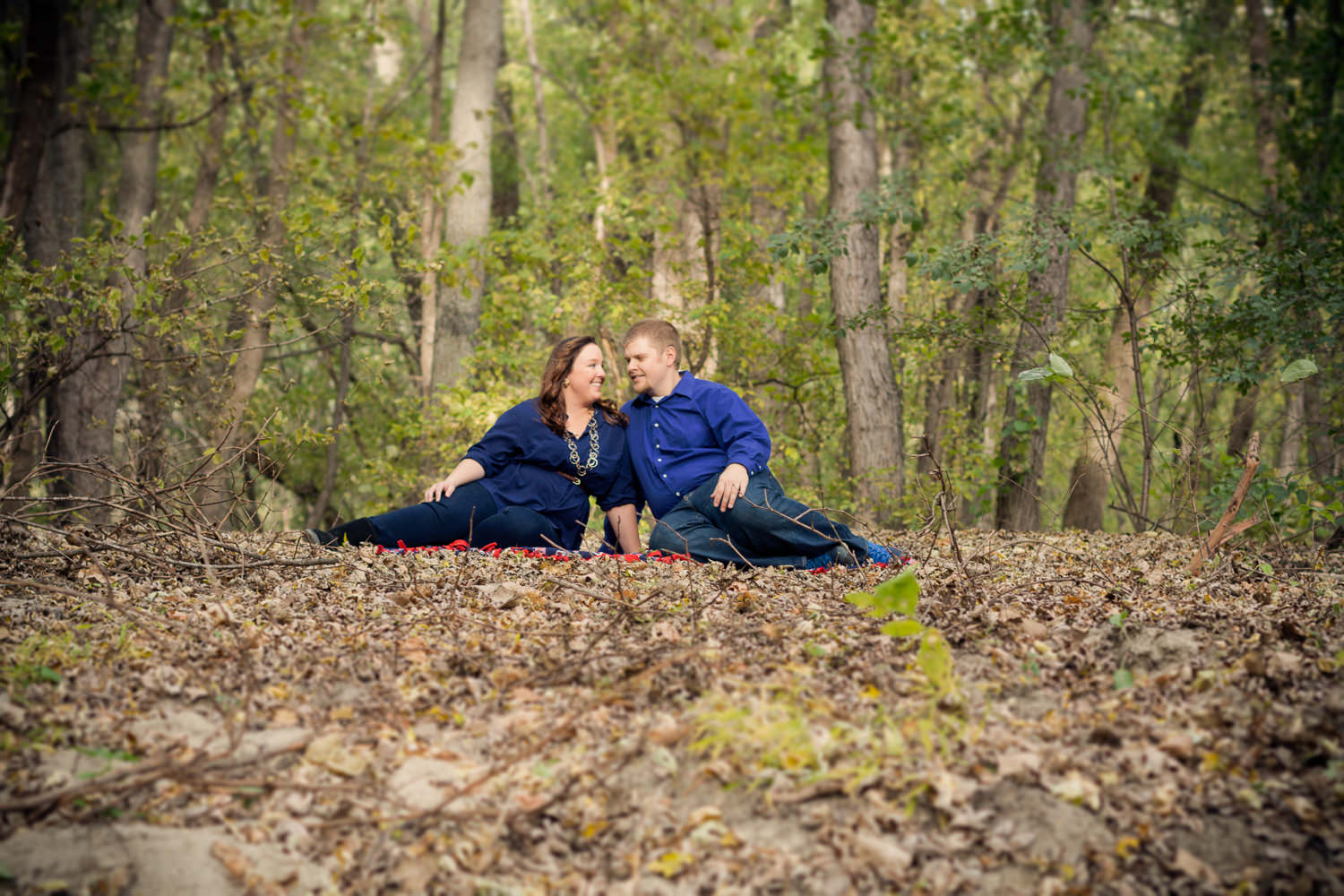 sitting on a blanket for your fall outdoor engagement pictures in belle plaine mn