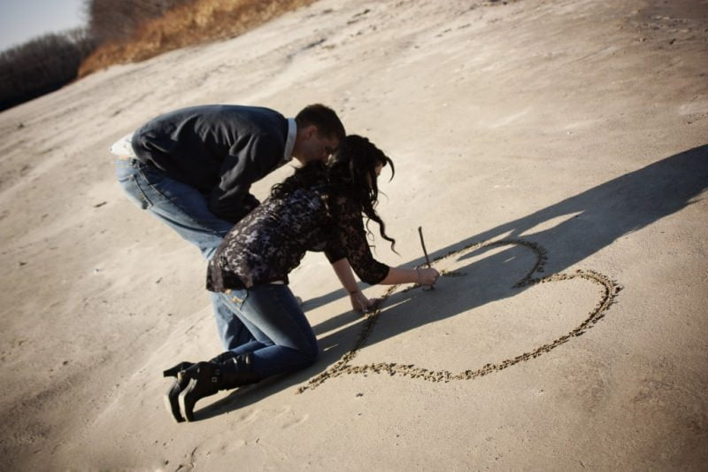 a couple draws a heart in the sand for their engagement pictures