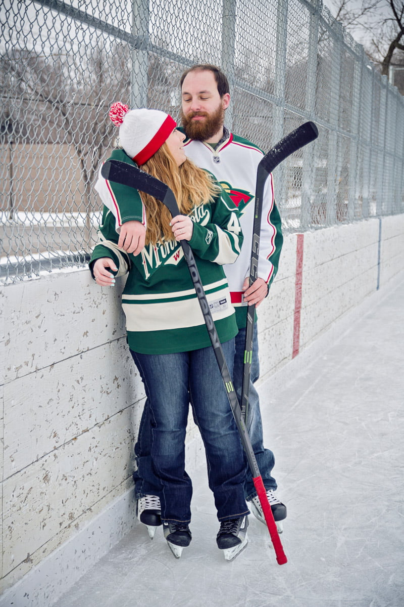a couple poses with hockey sticks for outdoor winter portraits
