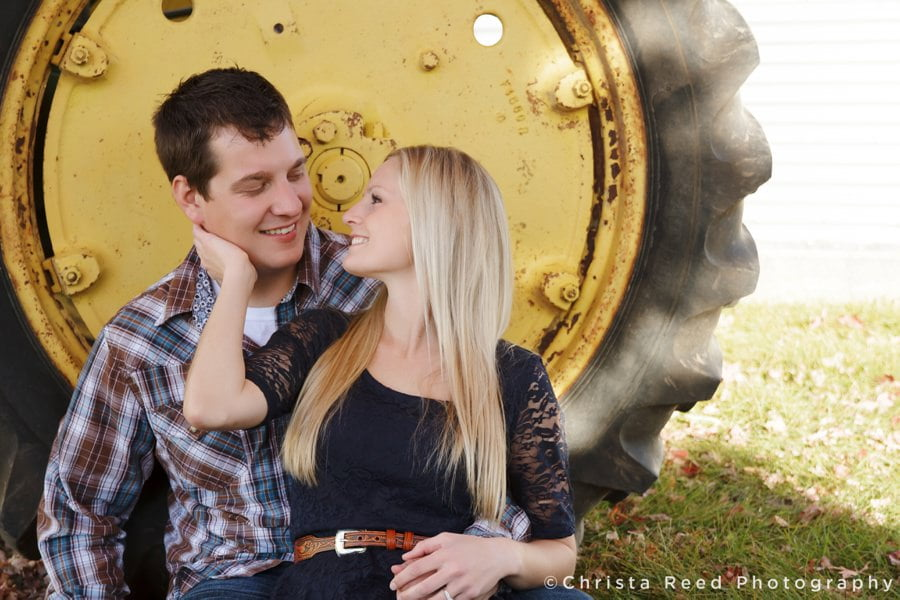 couple on a farm with a tractor in belle plaine minnesota for their engagement pictures