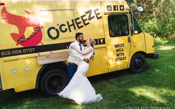 couple poses with o'cheeze food truck at their stacey Minnesota wedding