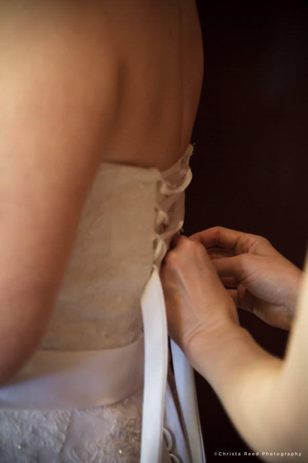 Minnetonka wedding photographer wedding dress being laced