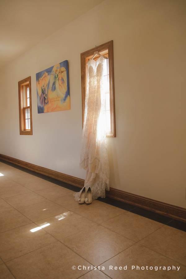 wedding dress in a window with sunlight shining in mankato