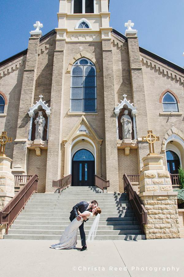 bride and groom kiss in front of church mankato