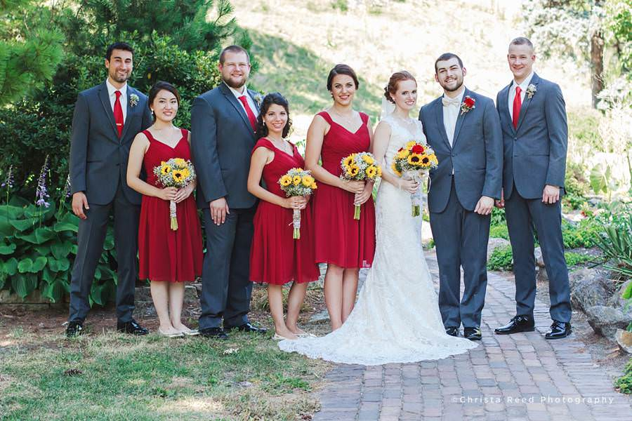red resses, grey suits and sunflower bouquets for wedding party