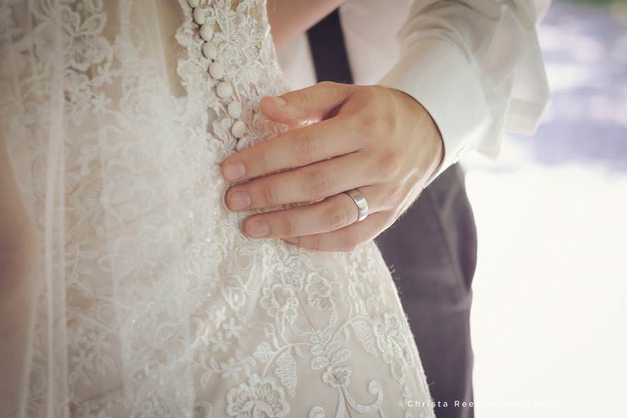 close up lace wedding dress and groom's ring