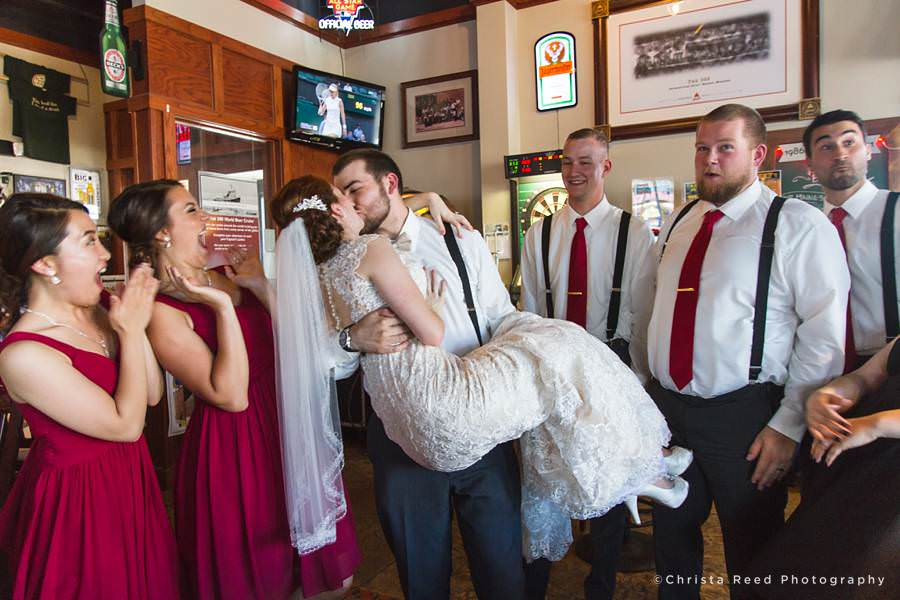 happy wedding party with bride and groom kissing