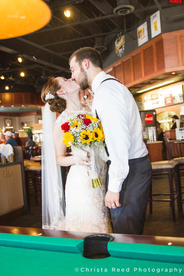 bride being kissed by groom with sunflower bouquet at pub500 in mankato
