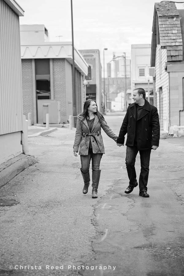 a couple holds hands and walks down an alley in shakopee minnesota