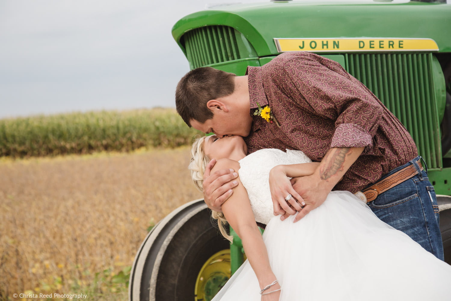 a couple kisses at their farm wedding with a john deer tractor and cornfield in the background