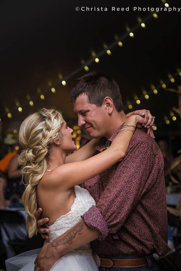 a couple has their first dance at a Minnesota wedding under a tent on the farm