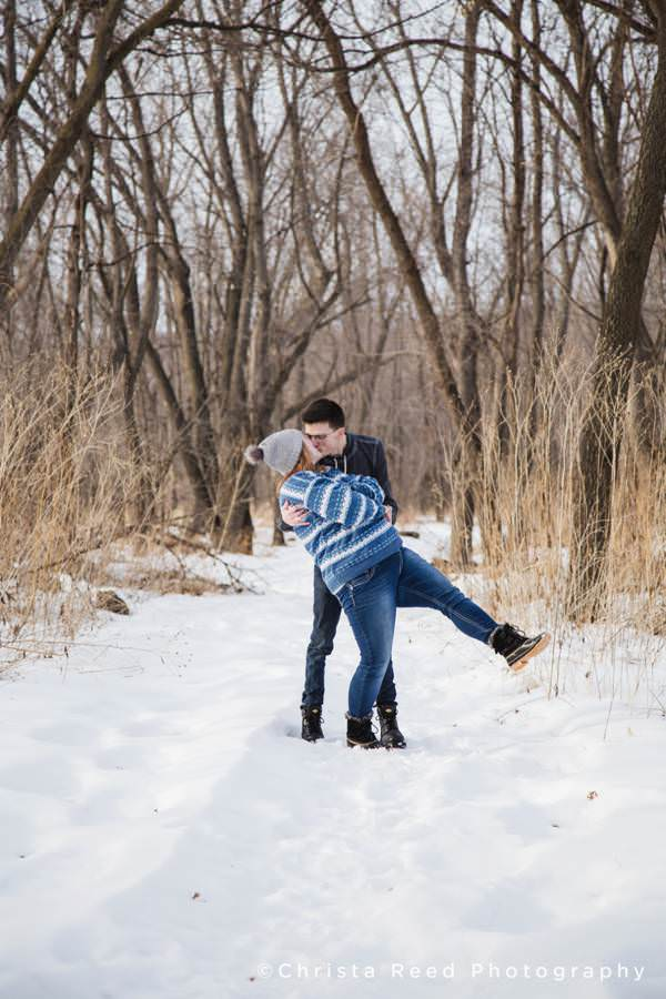a man dips and kisses his girlfriend for their portrait by Minnesota Couples Photographer