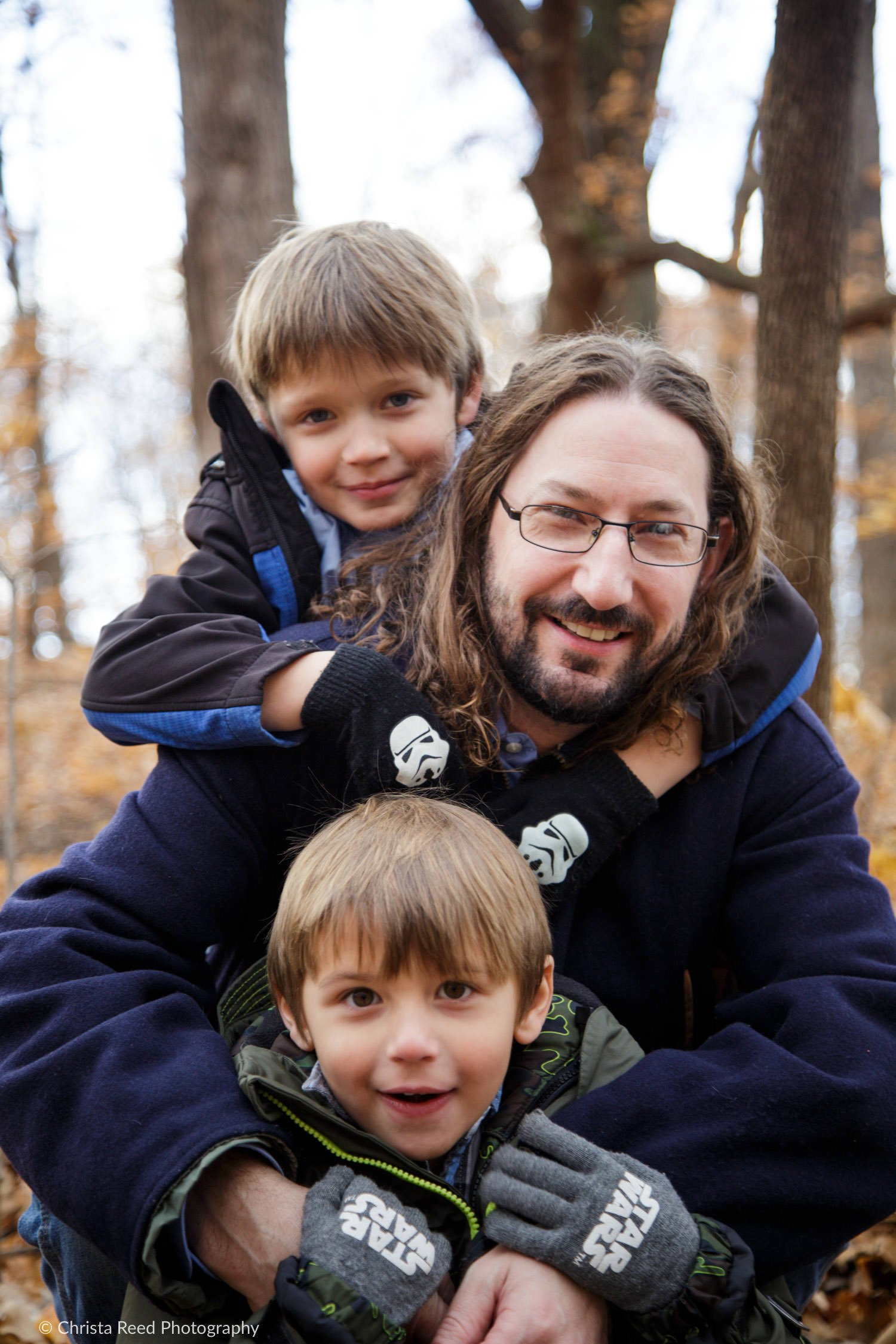 father and his two sons have portraits with a family photographer in chanhassen