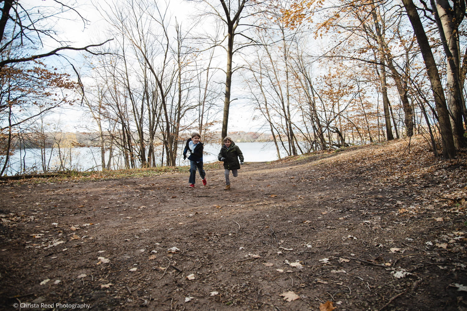 two boys run and play at Lake Ann for their fall portraits in Chanhassen