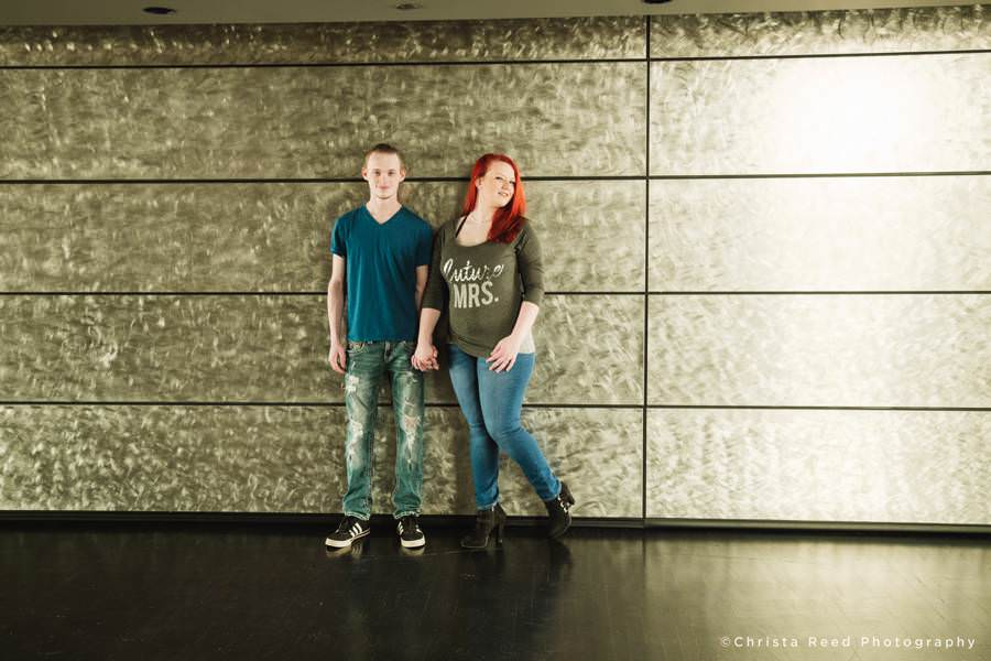 a modern silver wall contrasts a couple's blue jeans and t-shirts for their Guthrie Theatre Engagement pictures