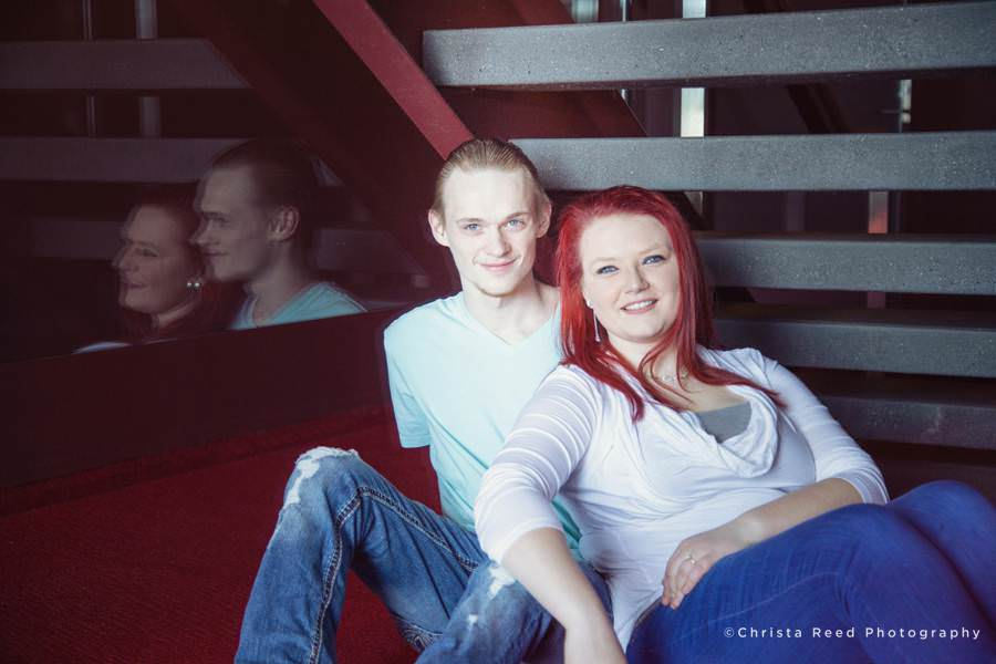 a couple sits under the stairs for their Guthrie Theatre Engagement pictures