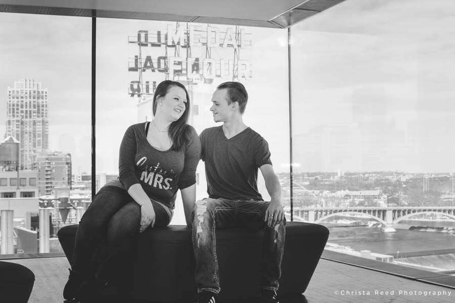 couple poses with the minneapolis skyline for their Guthrie Theatre engagement shoot