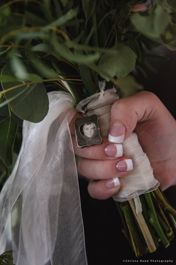 a wedding bouquet with a remembrance charm for a lost loved one
