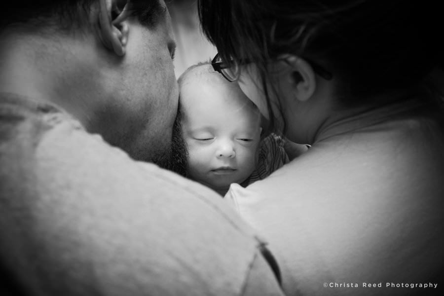 kissing sleeping baby at newborn photography session