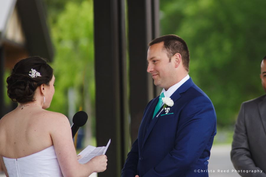 A groom smiles as the bride reads vows at their wedding ceremony in Huber Park Shakopee Minnesota