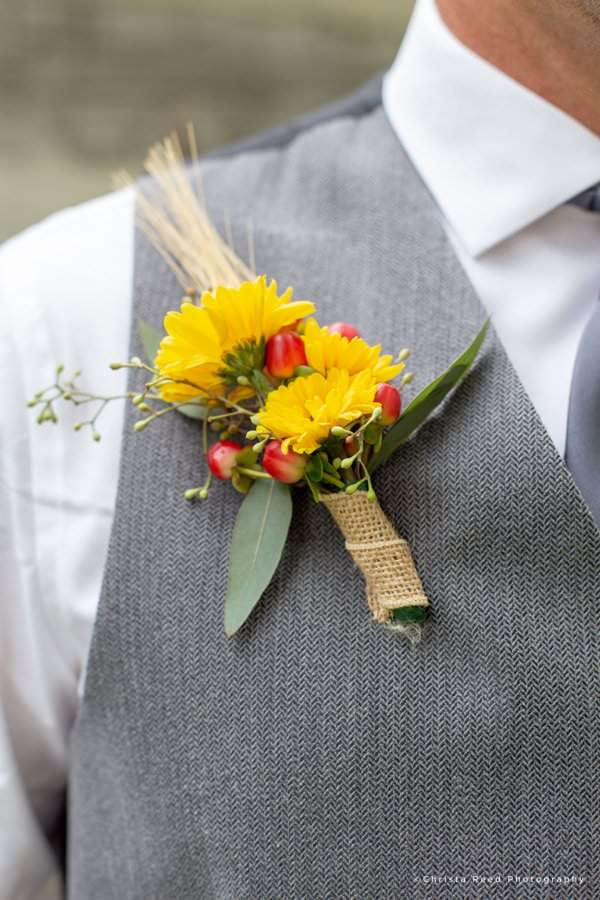 a groom's boutonniere with sunflowers and red berries for a Le Sueur wedding