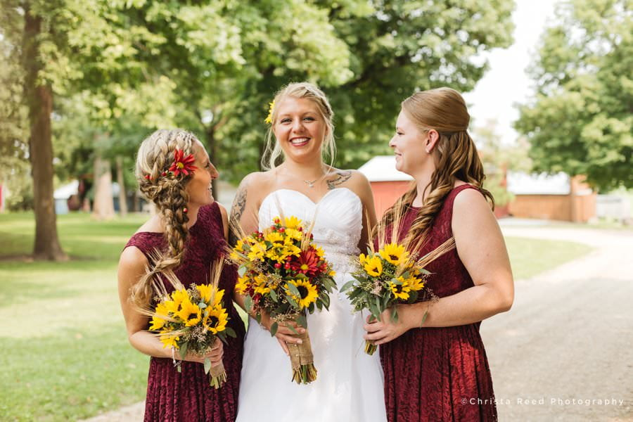 an august wedding with sunflower bouquets and red bridesmaid dresses