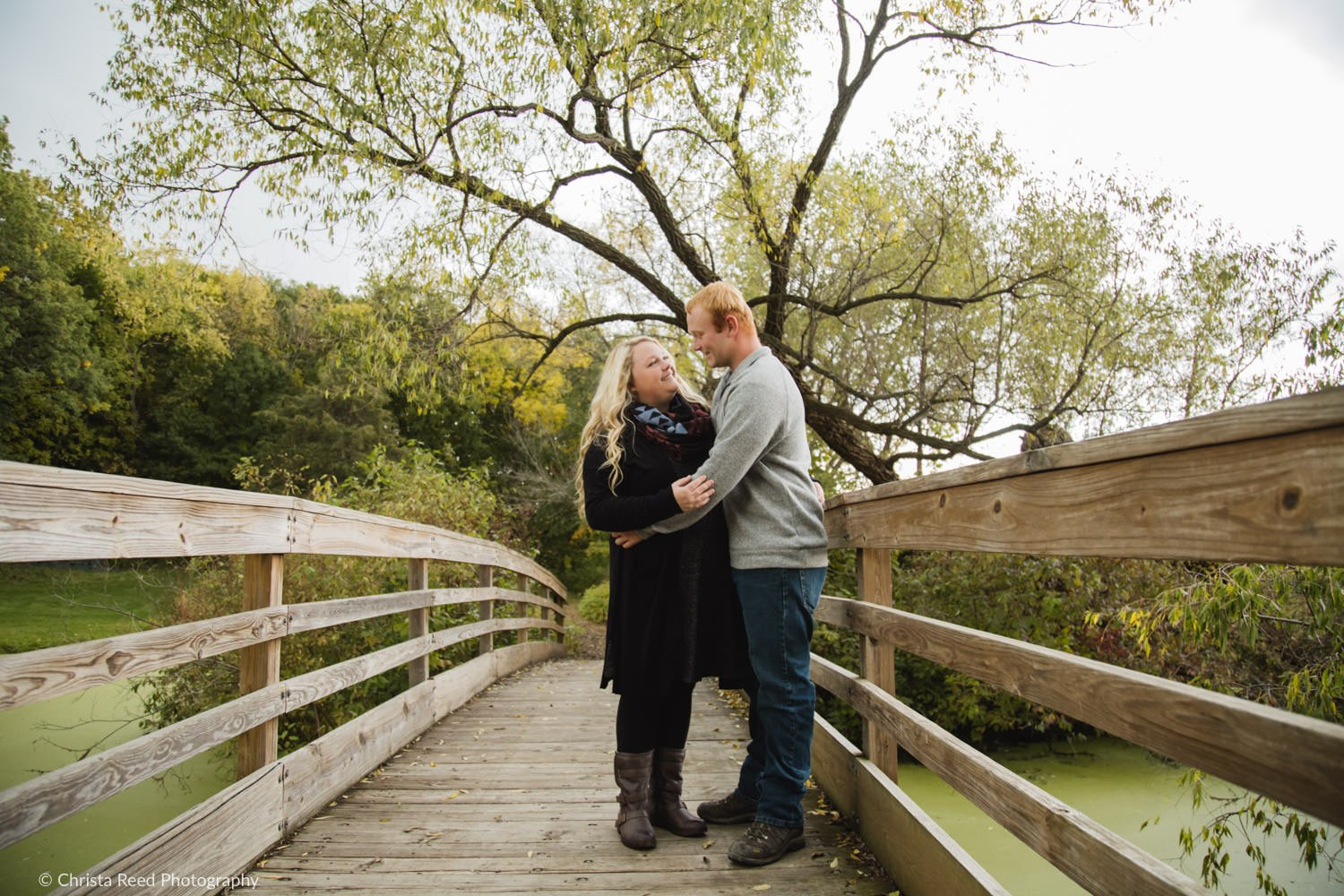 a couple stands on a bridge for their chaska engagement shoot