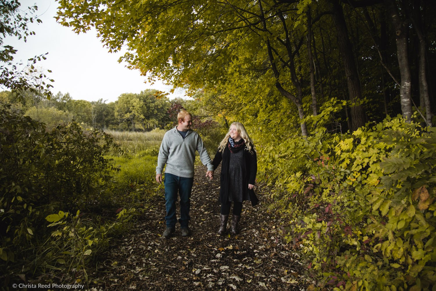 a couple walks in the woods for their chaska engagement shoot