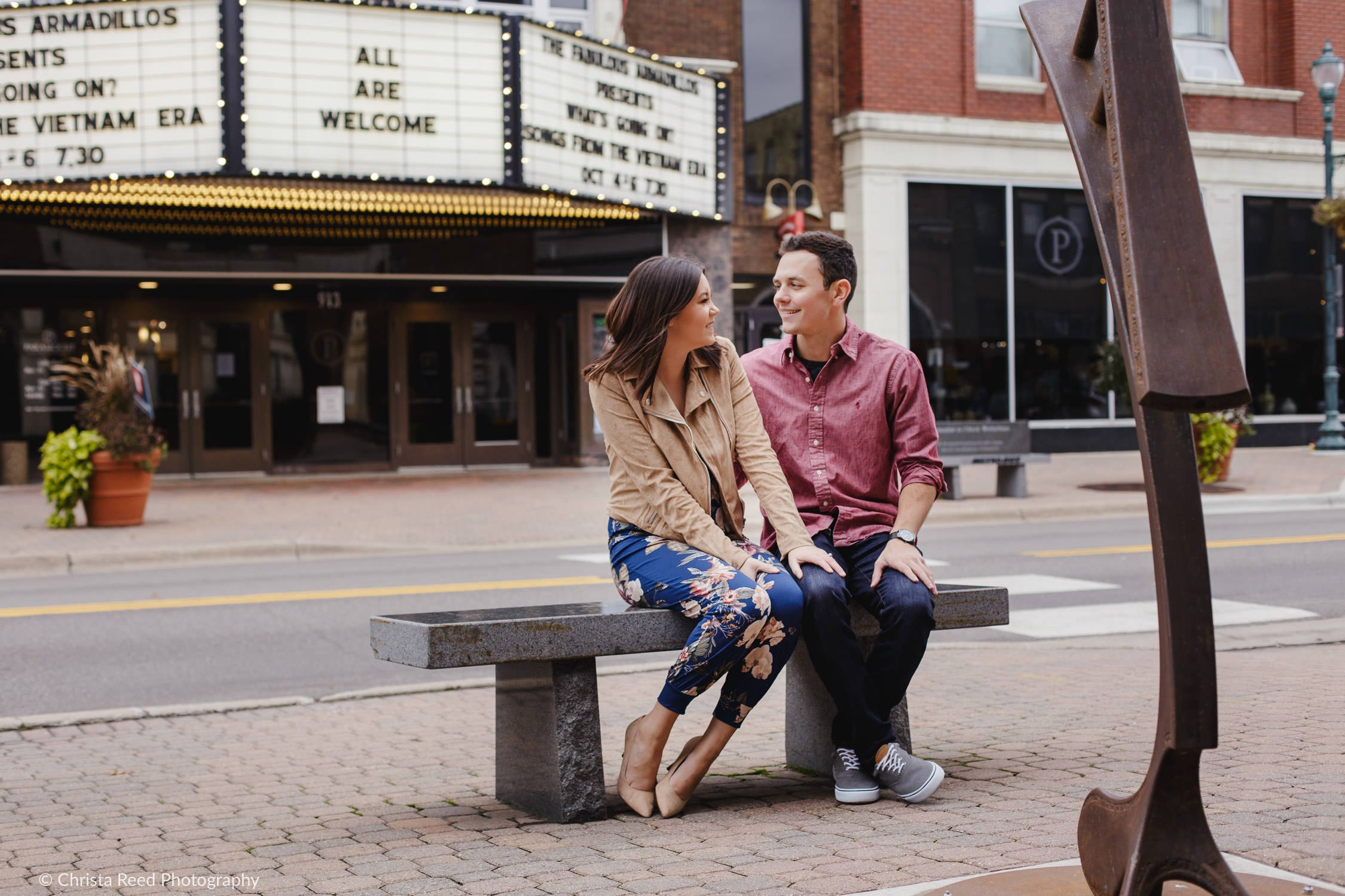 a couple poses in downtown st cloud quarry park engagement shoot