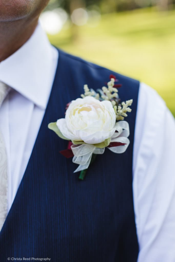mens boutonniere with eucalyptus leaves and navy blue vest