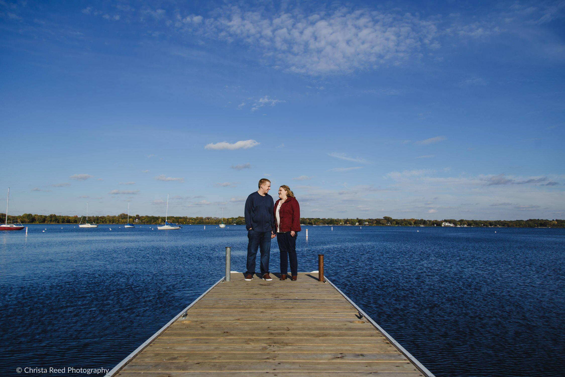 a couple stands on the dock for their white bear lake engagement shoot