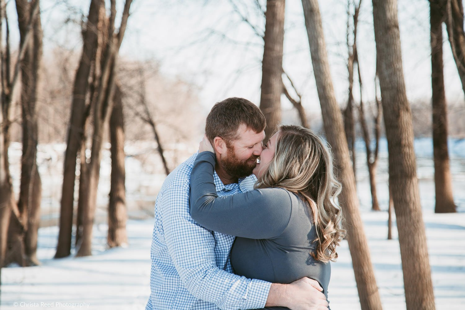 kissing in the woods for your engagement shoot in carver mn