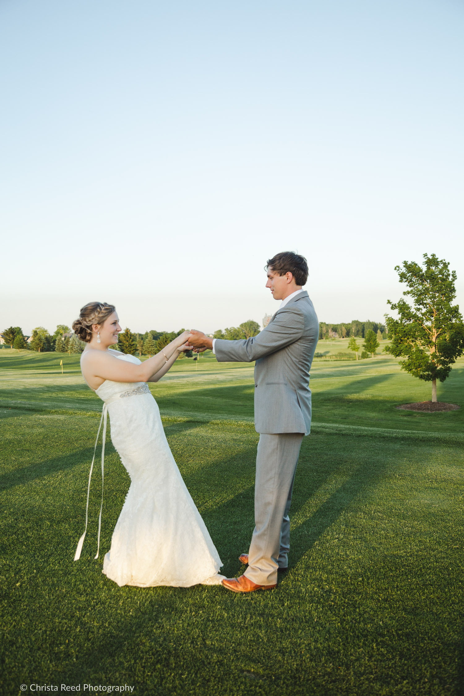 A playful wedding portrait on the green at Ridge of Sand Creek.