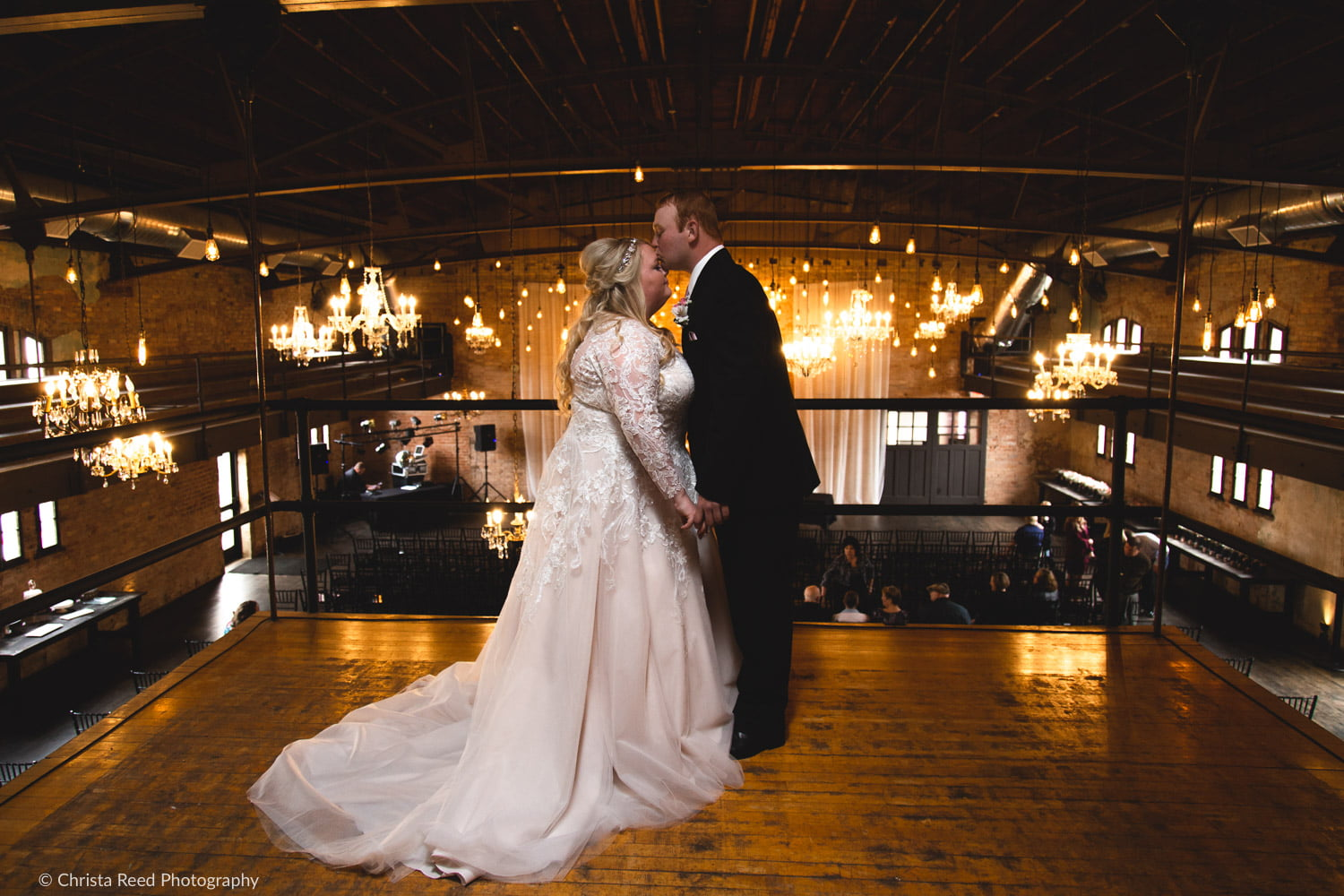 a couple stands on the balcony for their wedding portraits at the Capitol Room in St. Peter Minnesota