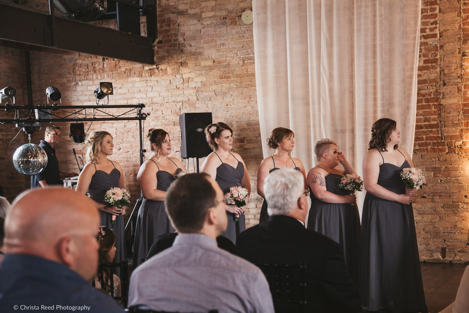 bridesmaids get emotional during a wedding ceremony at the Capitol Room St. Peter