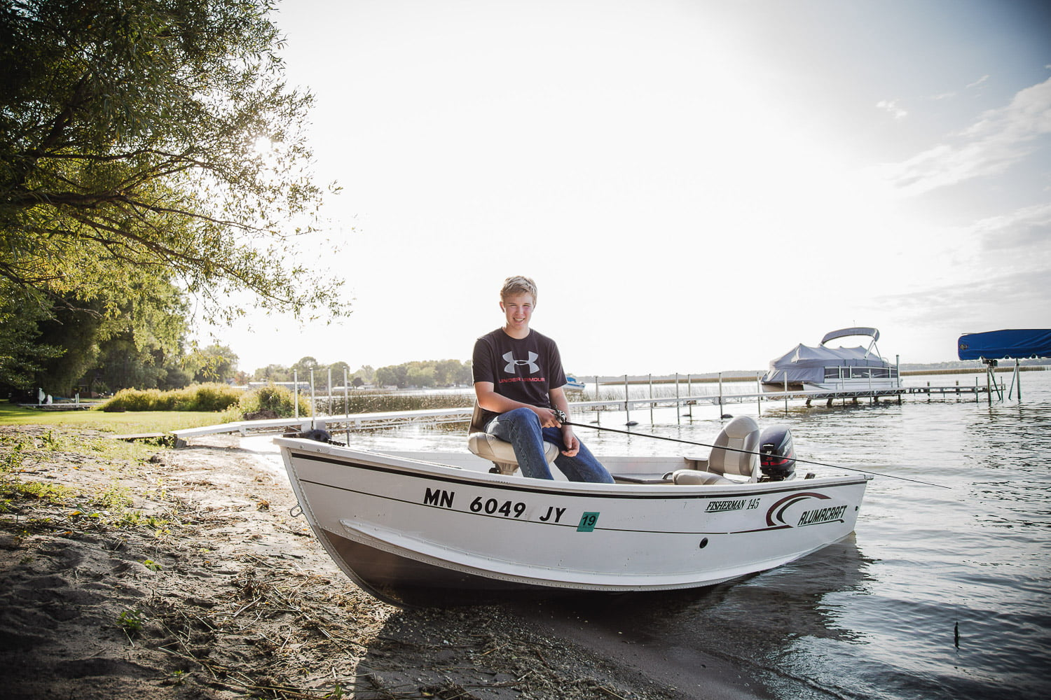 a teenager goes fishing for senior pictures