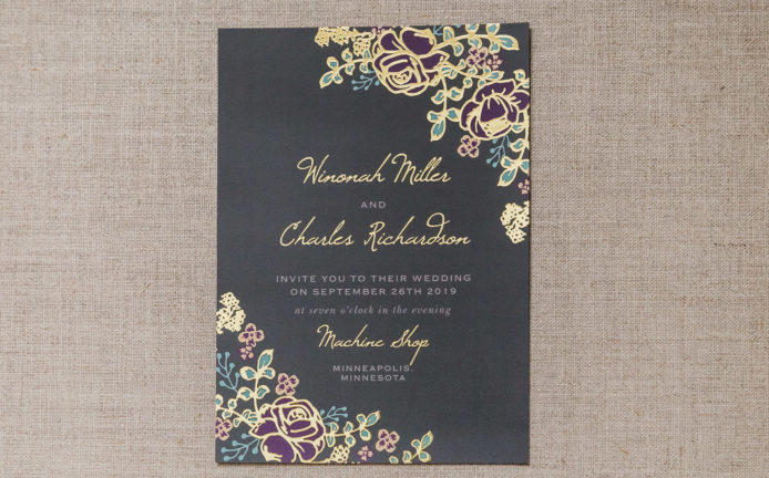 gold foil wedding invitation with flowers and black paper