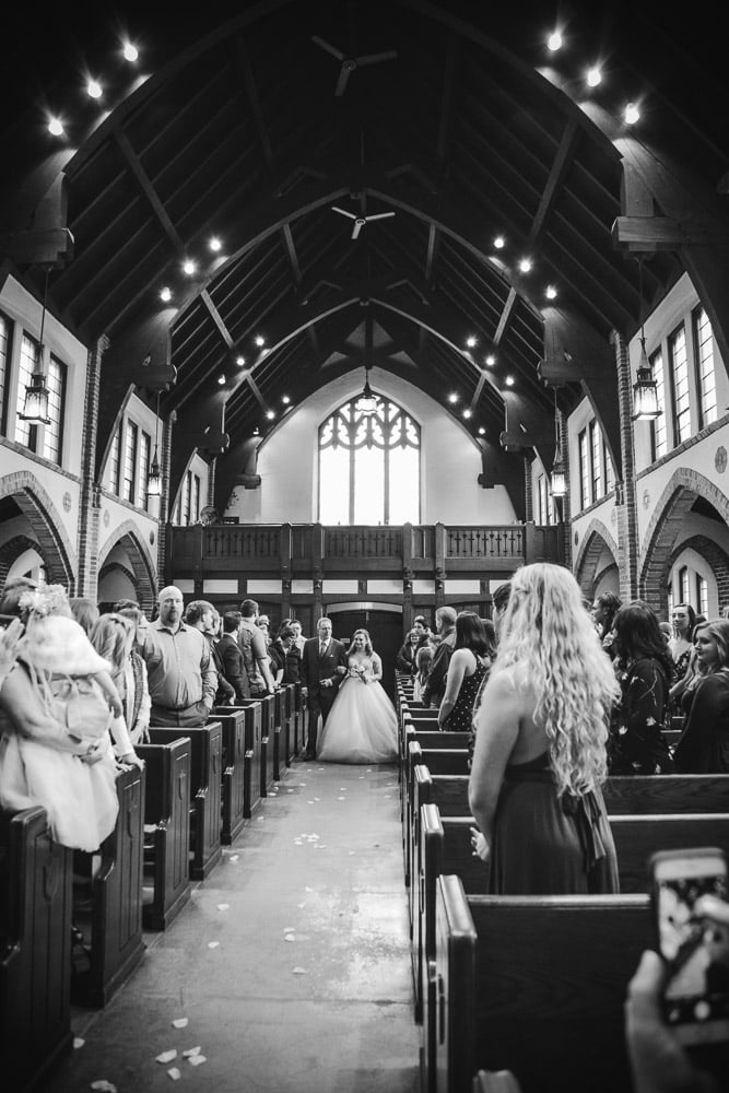a bride walks down the aisle under the vaulted ceiling of Grace University Lutheran in Minneapolis