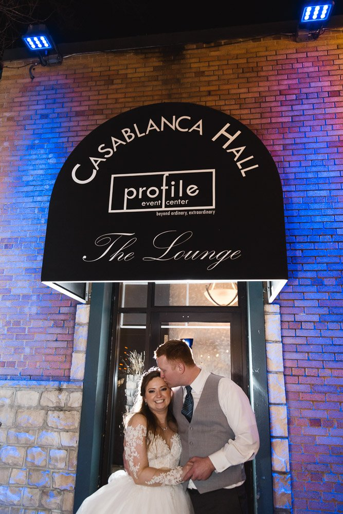 a couple stands under the Casablanca Hall awning at Profile Event Center