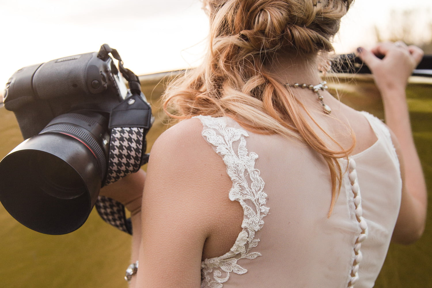a wedding photographer poses with a camera