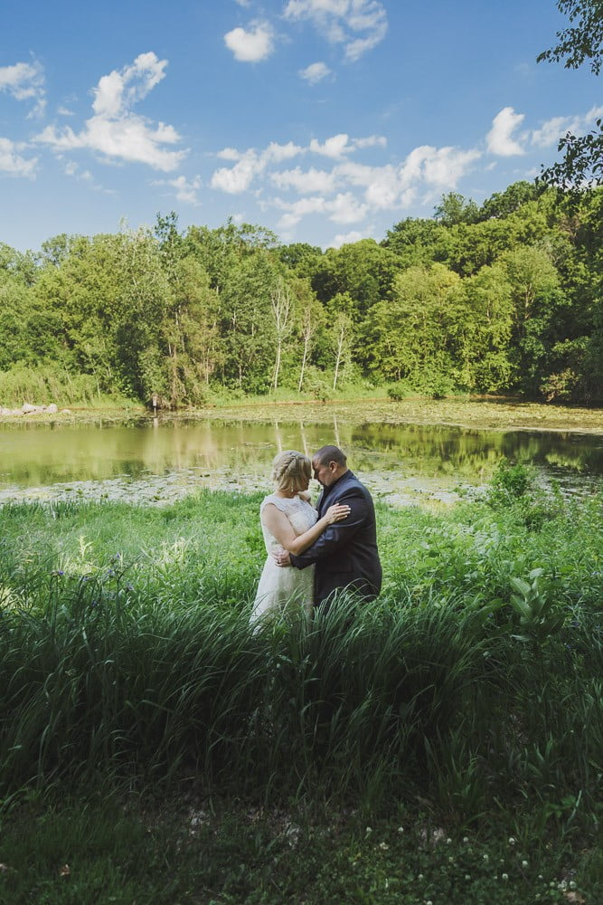 a Minnesota couple stands in a field for portraits at their intimate wedding in nature