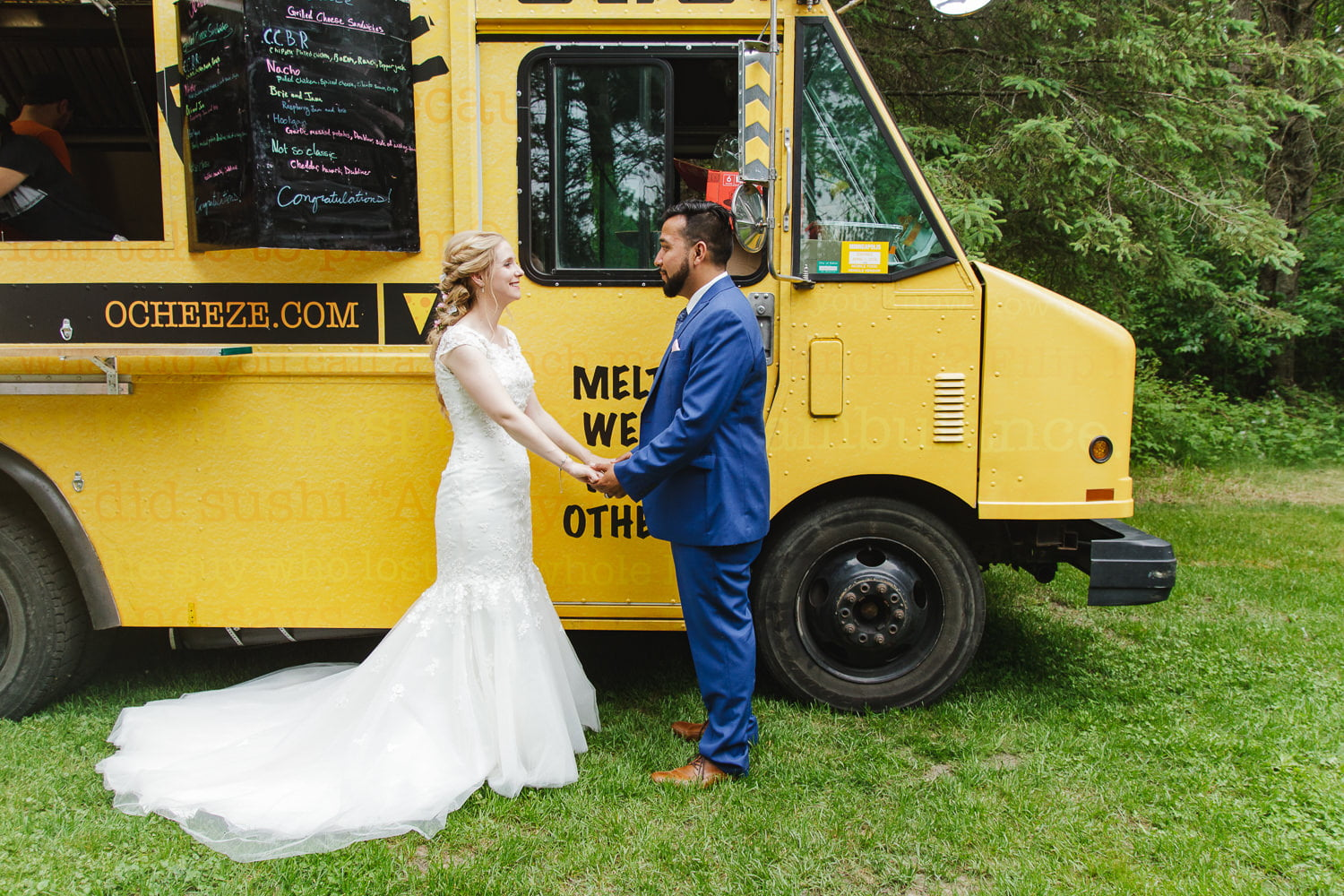 a couple stands by the o'cheeze food truck at their outdoor wedding reception
