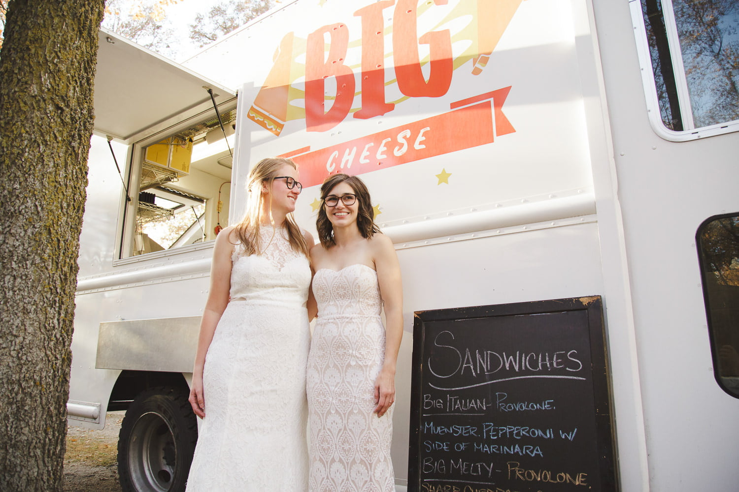 couple stands next to a food truck at their wedding