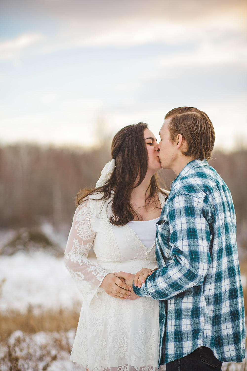 a couple kisses for their romantic portraits at sunset
